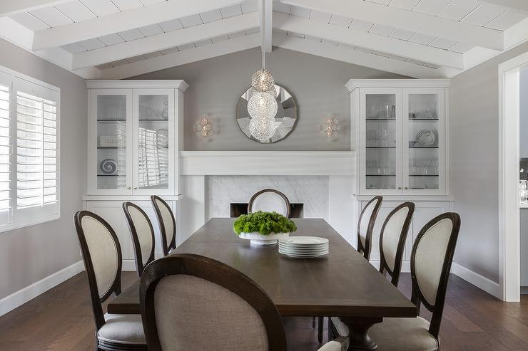 Under A White Vaulted Plank Ceiling Dark Stained Dining Table Sits Surrounded By Cream Found Back French Chairs Placed In Front Of Fireplace