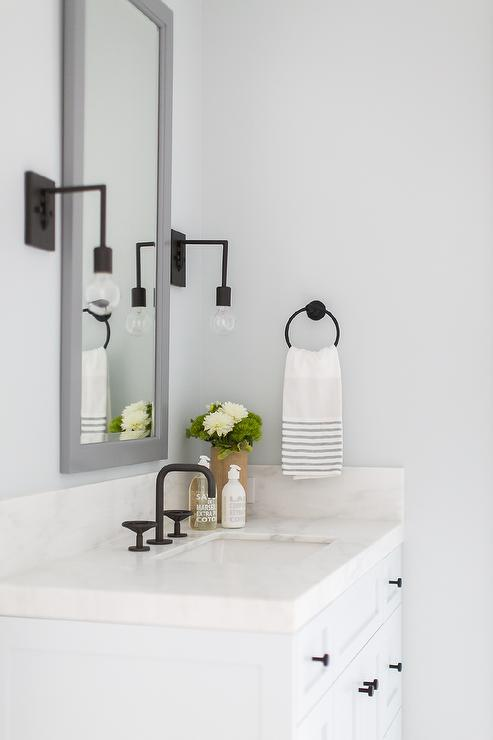Lovely white and gray powder room features a tall gray framed vanity mirror flanked by oil rubbed bronze Edison sconces mounted to a pale gray wall above a ...