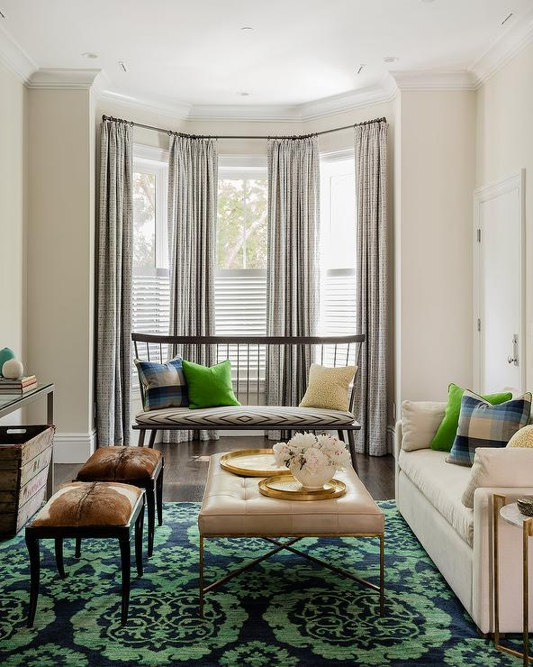 Your Eyes Will Immediately Be Drawn To A Green And Blue Medallion Rug Placed Beneath Light Taupe Leather Tufted Ottoman Flanked By Side Cowhide