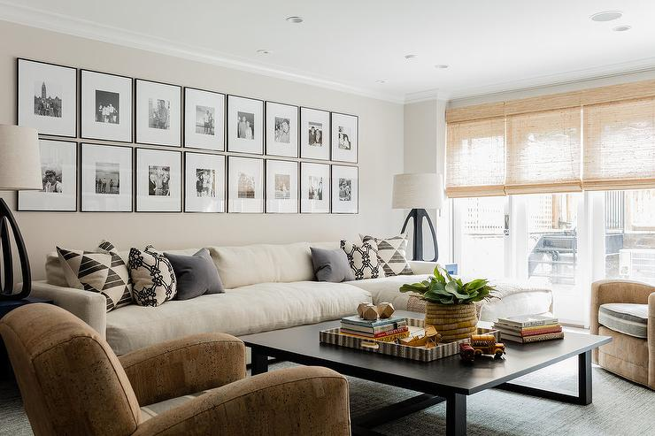 prodigious Living Room With Cream Sofa Part - 1: Two rows of framed black and white photographs are mounted to a cream wall  above a long cream sofa finished with a chaise lounge and topped with cream  and ...