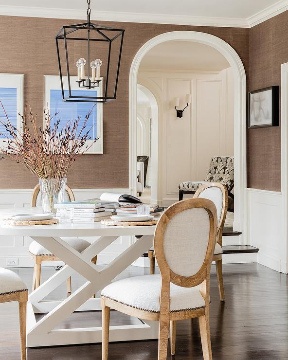 Welcoming White And Brown Dining Room Is Lit By A Darlana Medium Lantern  Hung Above A Round White Dining Table Seating French Round Back Dining  Chairs In ...