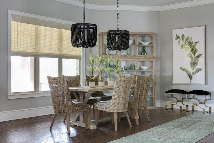 Gorgeous Trestle Dining Table Paired With Wicker Chairs On Hardwood Floors Next To A Green Runner
