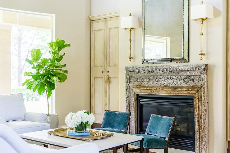 A Beveled Mirror Flanked By Cawdor Stanchion Wall Lights Hangs Above An  Antique Wood Ornate Fireplace Mantel Flanked By Bifold Recessed Cabinet  Doors.