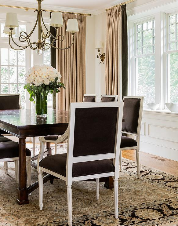 Dark Brown Velvet French Dining Chairs Sit On A Tan And Wool Rug Surround Wood Table Illuminated By Scroll Chandelier