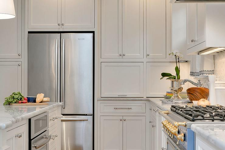 A Stainless Steel French Door Refrigerator Is Recessed Beneath White Shaker  Cabinets Adorned With Nickel Hardware And Beside White Cabinets Fixed Above  And ...