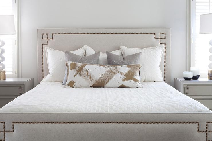 Elegant Gray Bedroom Boasts A Serena U0026 Lily Octavia Bed With Nailheads  Dressed In White Bedding Accented With A White And Gold Lumbar Pillow  Placed In Front ...