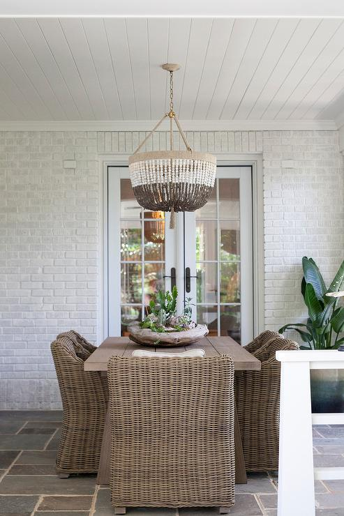 A Brown And White Beaded Chandelier Hangs From A White Beadboard Ceiling  Over Brown Trestle Dining Table.