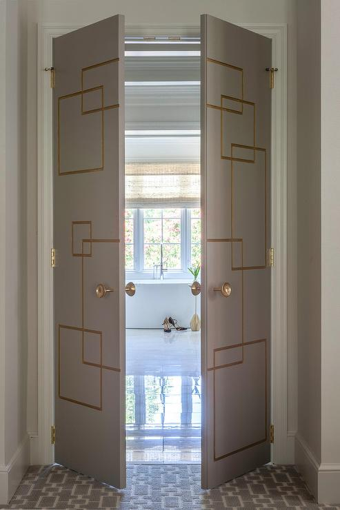 Gold And Gray Bi Fold Doors Open To Marble Floor Tiles Leading An Oval Freestanding Bathtub Paired With A Polished Nickel Mount Tub Filler