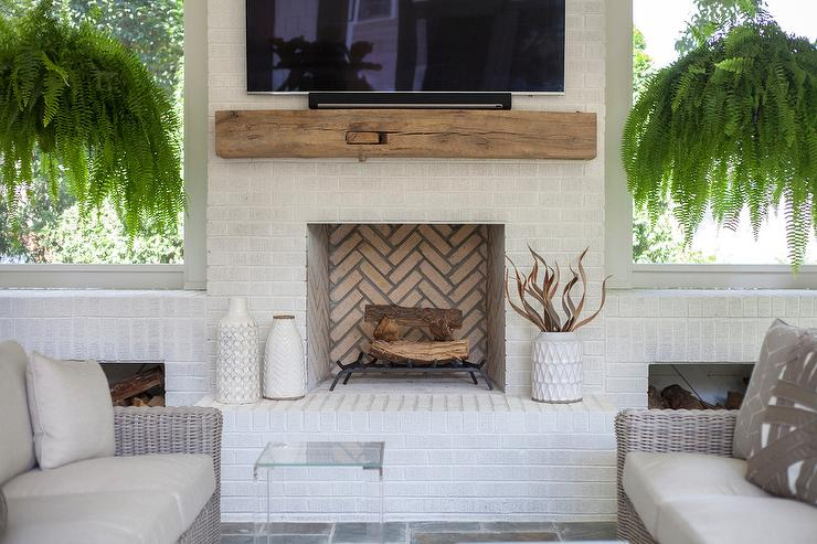 A white brick living room fireplace is accented with a chunky rustic wood mantel fixed beneath a flat panel television.