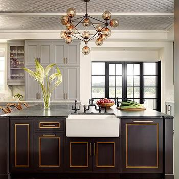 Gold And Black Kitchen With Thick White Marble Countertops