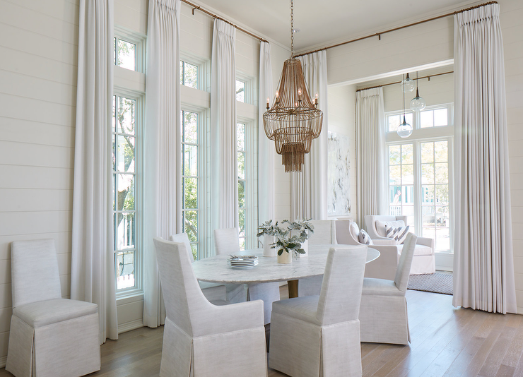 An Arteriors Maxim Chandelier Hangs Over An Oval Marble Top Dining Table Is  Seating Off White Slipper Dining Chairs In Front Of Windows.