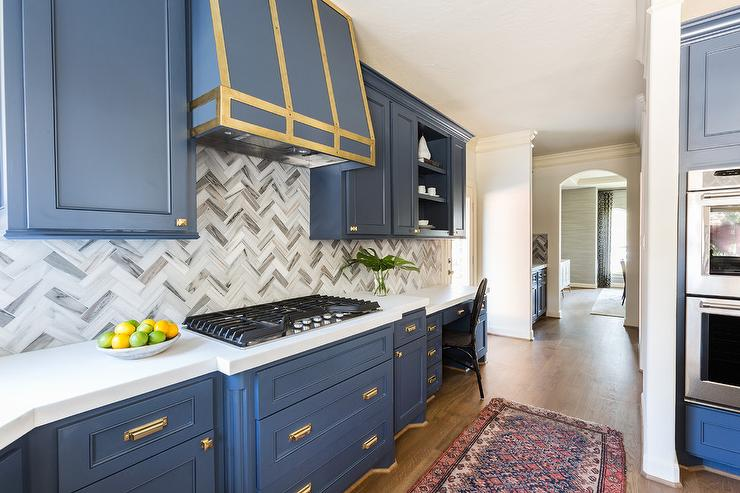 A Blue Hood Accented With Brass Straps Is Flanked By Cabinets Adorned Square Knobs And Mounted To Gray Marble Herringbone Backsplash Tiles