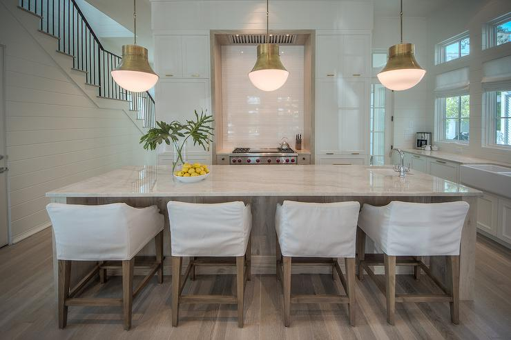 light gray stone countertop accenting a light stained oak island boasting a prep sink and polished nickel gooseneck faucet lit by three kelly wearstler