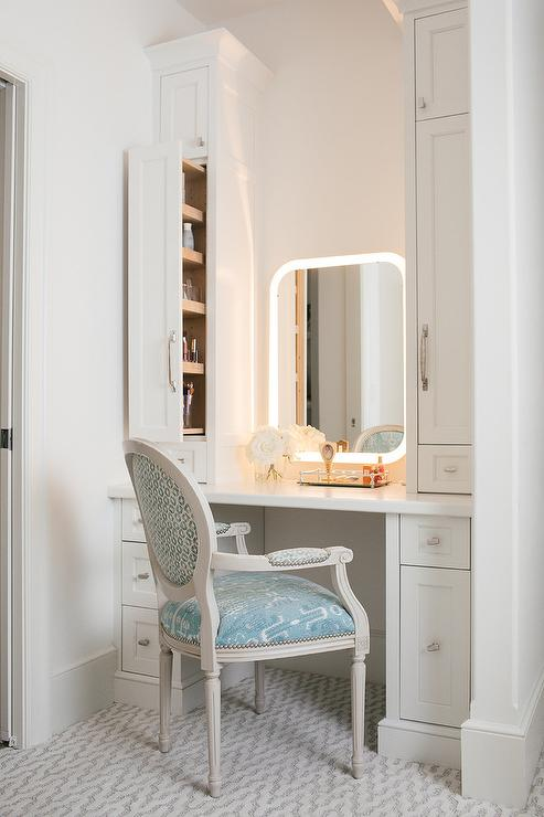 a curved light vanity mirror is flanked by white pull out cabinets accenting a white makeup vanity finished with satin nickel hardware a white quartz