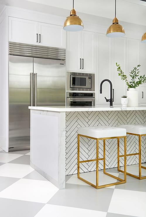 nuevo chi white u0026 gold counter stools sit on gray and white harlequin floor tiles at a white marble kitchen island accented with white herringbone tiles and
