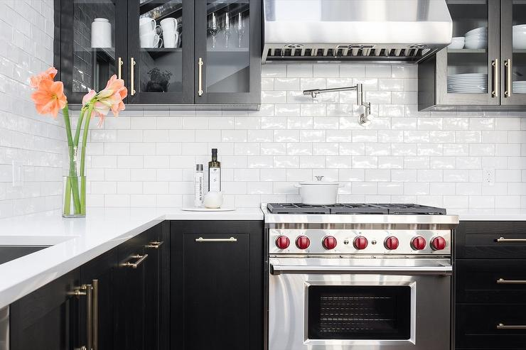 Ordinaire Black And White Transitional Kitchen Features Black Cabinets With Brass  Pulls And Glass Front Upper Doors.