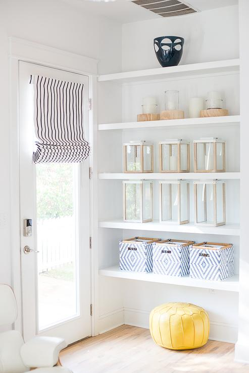 Cottage Living Room Features A Nook With Stacked White Floating Shelves.