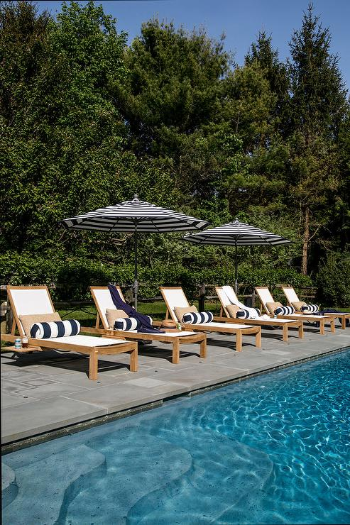Outdoor Pool Deck Designed With Teak Pool Loungers On Slate Tiles Accented  With Navy Blue Striped Bolster Pillows Under Matching Lounger Umbrellas.