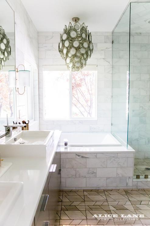Gray chandelier over marble subway tiled bathtub for Bathroom decor regina