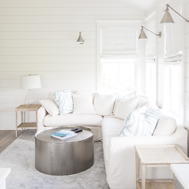 white slipcovered corner sectional with light wood end tables