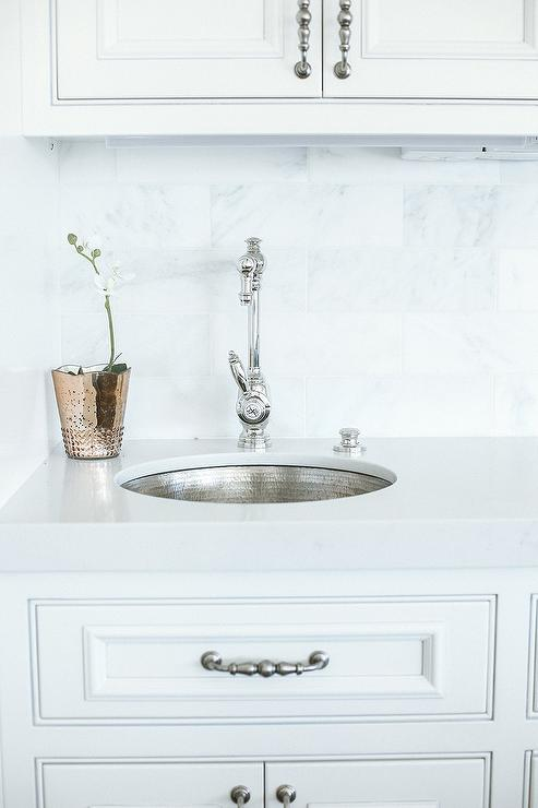 white pantry cabinets accented with satin nickel pulls are fitted with a round hammered metal sink with a polished nickel vintage style faucet