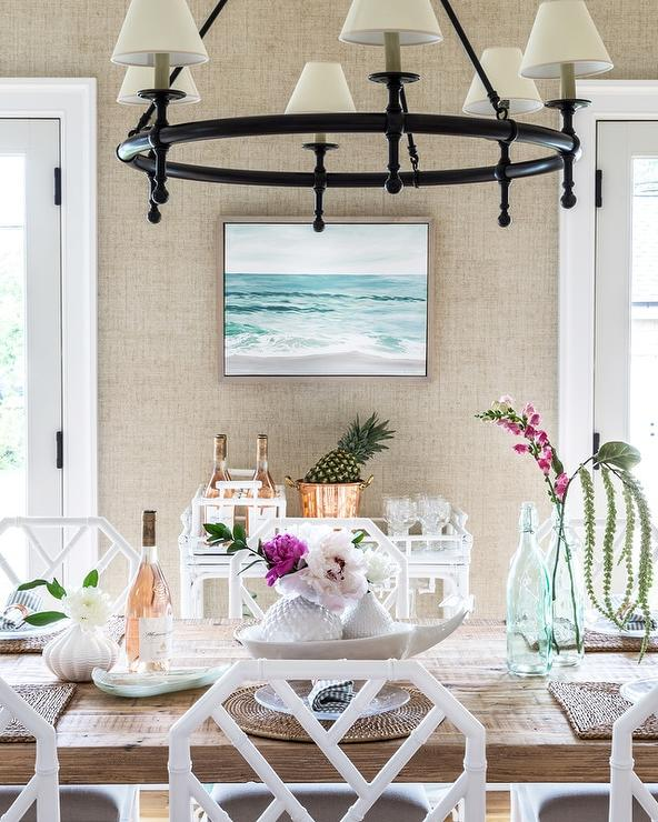 Faux White Bamboo Dining Chairs Surround A Wood Trestle Table Illuminated By Classic Ring Chandelier And Placed In Front Of Bar Car