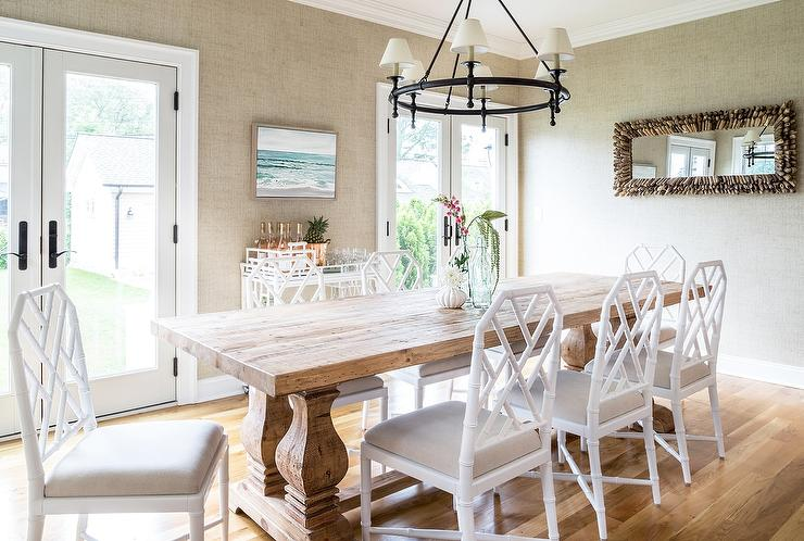White Bamboo Dining Chairs Topped With Tan Cushions Surround A Wood Trestle Table Placed Beneath Classic Ring Chandelier