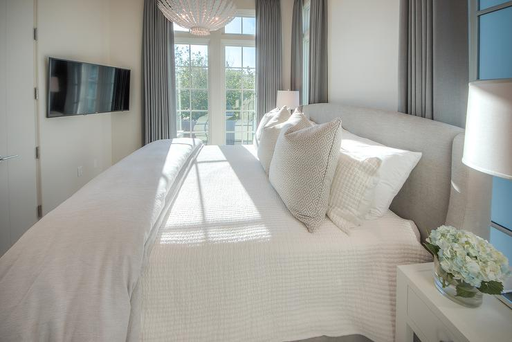 A Cottage Bedroom Is Fitted With All The Trimmings Such As A White Feather  Pendant Light Over A Gray Wingback Bed, White Lacquer Nightstands, And A  Wall ...