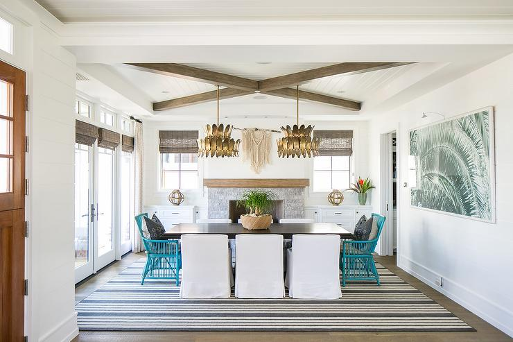 Arteriors Analise Chandeliers Elegantly Hang Over A Black Dining Room Table  With White Low Back Slipcovered Chairs Accented With Turquoise Blue Rattan  End ...
