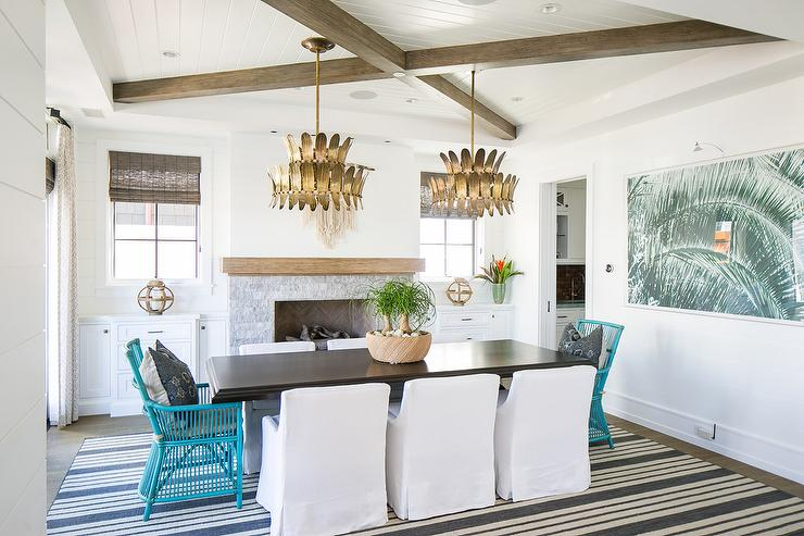 A Glamorous Dining Room Boasts Gold Arteriors Analise Chandeliers Over A  Black Dining Room Table With Turquoise Blue Rattan Chairs And White Low Back  ...