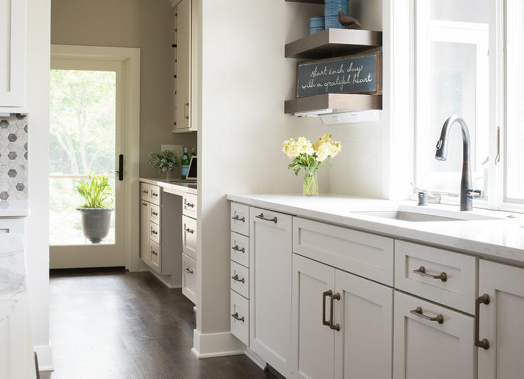 White Shaker Cabinets Accented With Satin Nickel Hardware And A Calcutta  Quartz Countertop Are Fitted With A Stainless Steel Sink And A Bronze  Gooseneck ...