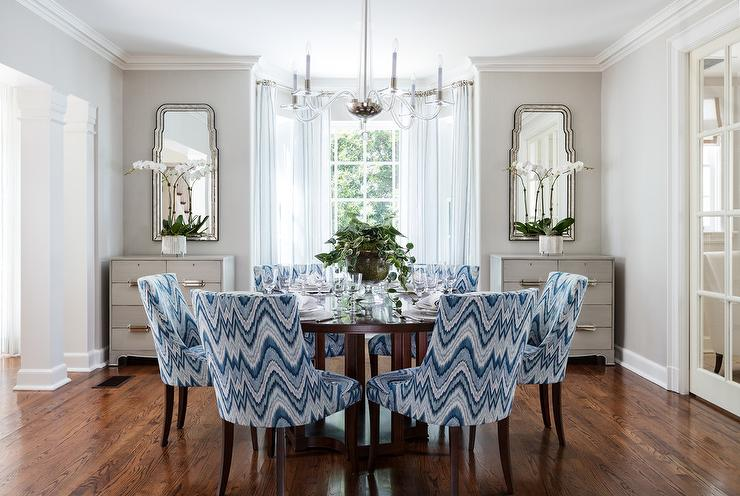 Blue Chevron Upholstered Dining Chairs Surround A Round Cheery Wood Table Illuminated By Robinson Large Chandelier
