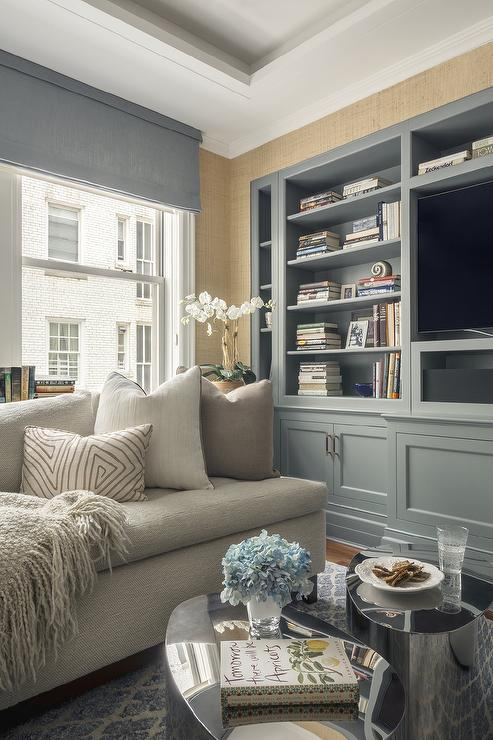 Gray Tufted Sectional With Neutral Pillows And A Throw Blanket Face A Round  Silver Coffee Table Next To Blue Built Ins, Gold Grasscloth Wallpaper Walls  ...