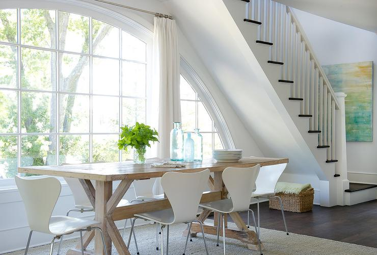 Dressed In White Pleated Curtains And Fixed Beneath A Staircase West Elm Scoop Back Chairs Surround Caramel Stained Trestle Dining Table Placed On