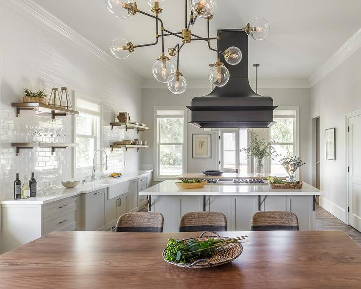 A Black Kitchen Vent Hood Stands Out Amongst Light Gray Shaker Cabinets In  A Transitional Kitchen Over A Center Island With White Quartz Countertops  And ...