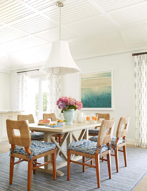 natural woven dining chairs accented with blue chevron cushions sit on a blue striped rug around a light gray wood trestle dining table