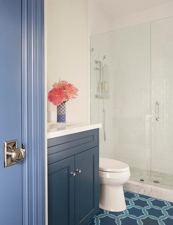 a blue door opens to a lovely blue bathroom featuring a blue shaker bath vanity adorned with nickel hardware and topped with a white quartz countertop