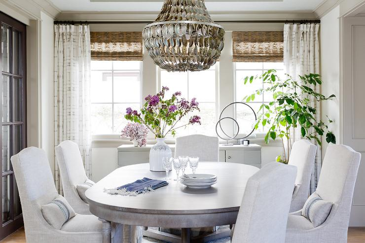 Surrounded By Gray Slipcovered Dining Chairs, An Oval Wood Dining Table  Sits Beneath A Shells Chandelier And In Front Of A Window Covered In Bamboo  Roman ...