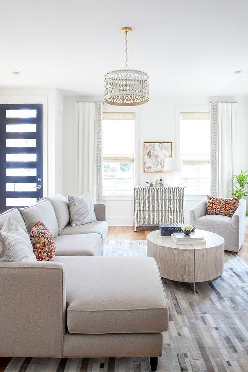 Transitional Naturally Lit Living Room Features A Light Gray Sectional  Paired With A Round Light Gray Oak Coffee Table Under A White Trellis Drum  Light ...