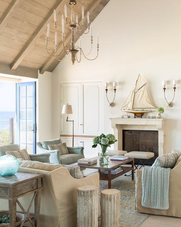 gorgeous blue and beige cottage living room is illuminated by a tiered french chandelier hung from a gray plank vaulted ceiling above a wood coffee table