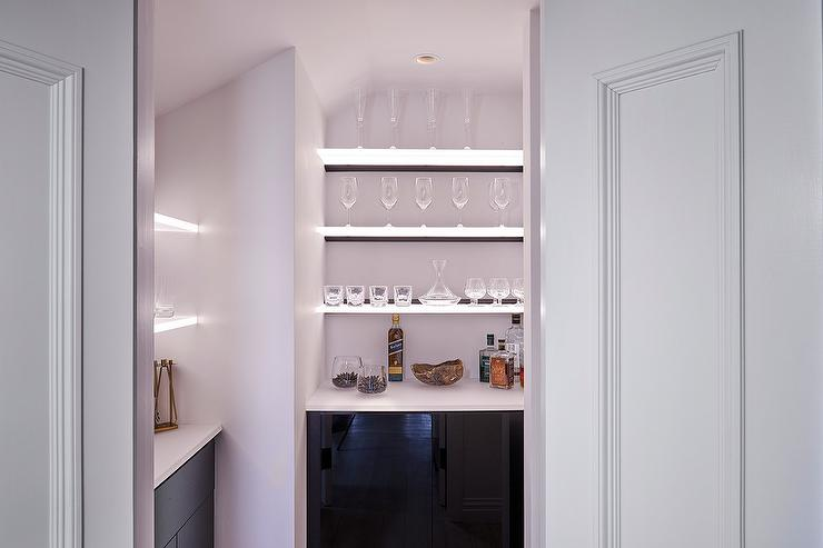 wet bar pantry features glossy black bar cabinets and floating shelves lit with led lights