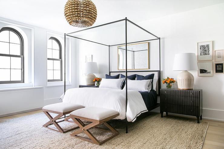 stylish bedroom is furnished with wooden x stools placed on a seagrass rug at the foot of an iron canopy bed