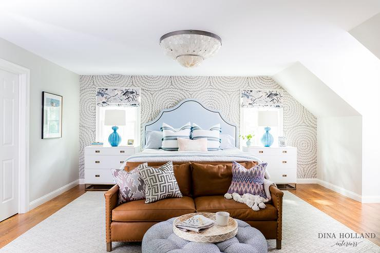 7baca261d61c3 Aerin Gannet Table Lamps display a bold blue finish atop white 3 drawer  nightstands against bedroom windows dressed in blue and gray roman shades.