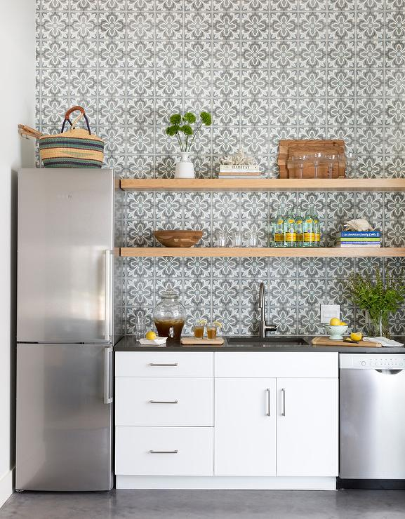 Small Kitchen Features A Slim Profile Stainless Steel Refrigerator Placed On Dark Gray Cement Floor Tiles Against An Accent Wall Clad In And Blue