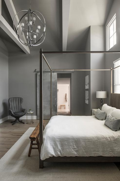 wood canopy bed with slate blue pillows