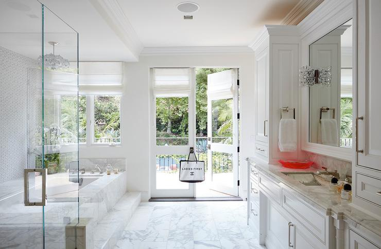 French Doors Step Out Into A Balcony From A Master Bathroom With Marble  Floors, A Marble Clad Bathtub With Steps, And Glass Enclosed Walk In Shower.