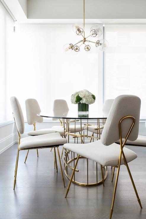 Chic Contemporary Dining Room Is Lit By A Glass And Brass Globe Chandelier  Hung Over An Oval Glass And Brass Dining Table Placed On An Ebony Stained  Oak ...