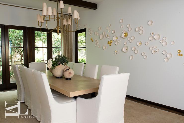 gold dining table with white slipcovered dining chairs