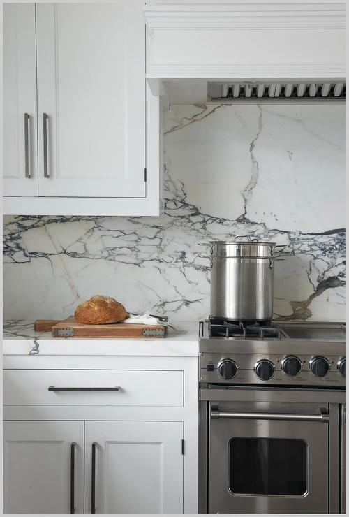 gray and white slab backsplash with stainless steel stove