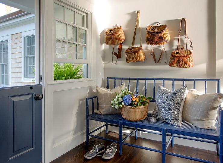 Decorative Baskets Hang From A White Wall Above A Blue Can Bench Placed In  A Mudroom Fitted With A Blue Bar Door.